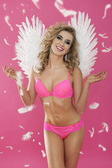 Sexy angel enjoying the falling feathers