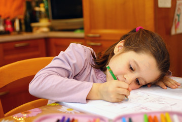 thoughtful young girl writes on her notebook