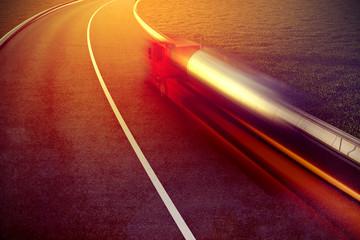 Fast truck on asphalt road motion blur