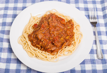 Plate of Spaghetti and Meat Sauce on Blue Plaid Placemat