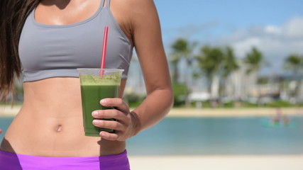 Fitness woman drinking green vegetable smoothie