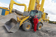 worker in red uniform on phone at  buldozer