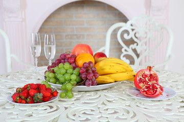 Grapes, bananas, a pomegranate, an orange and apples and a straw