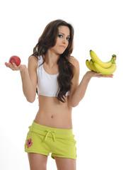 sportliche Frau mit Apfel und Bananen in der Hand
