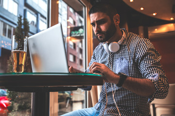 Young man sitting at cafe and using laptop.