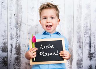 Liebe Mama, Sohn hält Tafel