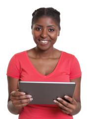Lachende Frau aus Afrika im roten Shirt mit Tablet