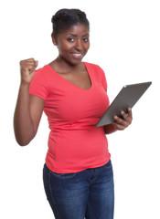 Frau aus Afrikaner im roten Shirt hat Spass mit Tablet