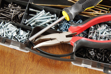 Screwdriver and pliers lie on a plastic box with many screws