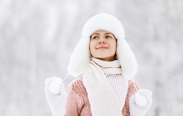 Happy pretty woman in sweater and hat enjoying the winter weathe