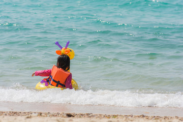 kid girl enjoying swimming in sea with rubber ring giraffe