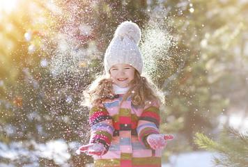 Joyful child having fun with snow in winter day