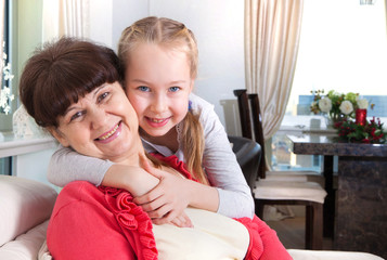 Senior lady with granddaughter hugging and smiling