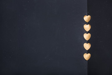 Gold heart stickers on dark texture background with blank space