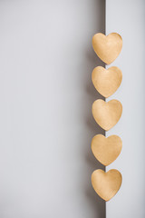 Gold heart stickers on grey textured background with blank space