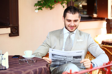Handsome man reading a newspaper
