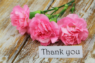 Thank you card with pink carnations on rustic wooden surface