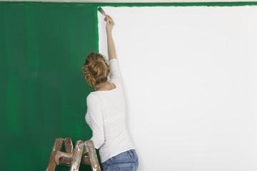 Frau mit Pinsel vor gruener Wand
