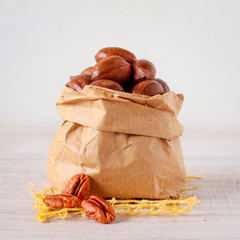 Pecan nuts in a paper bag on wooden table