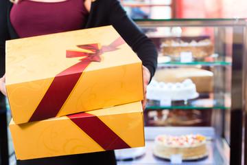 Frau präsentiert Tortenboxen einer Konditorei