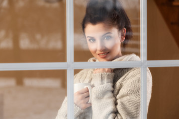 Woman drinking hot drink standing by the window