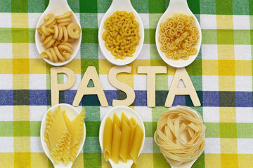 Pasta written with wooden letters and uncooked pasta on spoons