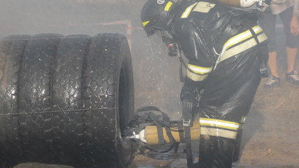 Firefighters in helmets and uniforms at exercises outdoors