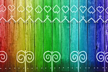 Rainbow colored wood wall with white pattern