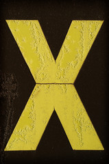 Yellow letter X covered with frost