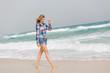 canvas print picture - Junge Frau geht am Strand spazieren