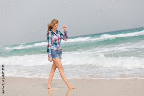 canvas print picture Junge Frau geht am Strand spazieren