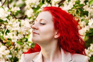 the girl with red hair in the blossoming garden