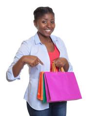Frau aus Afrika zeigt auf ihre Einkaufstaschen