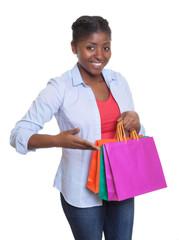 Frau aus Afrika präsentiert ihre Einkaufstaschen