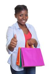 Lachende Frau aus Afrika freut sich über ihren Einkauf