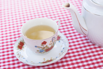 teapot and cup with tea on checkerboard background