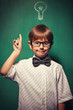 Little boy with glasses standing in front of chalkboard with bul
