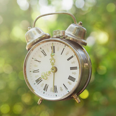 old clock alarm with natural green bokeh background