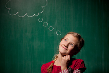 Little girl standing in front of chalkboard with cloud