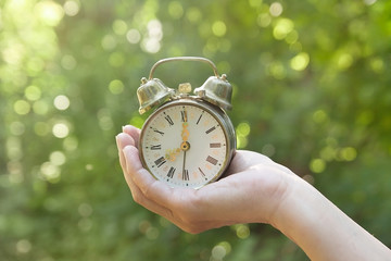 female hand holding old clock alarm with natural background