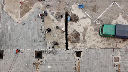 Workers stack paving slabs on city street, view from above