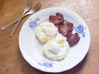 Breakfast plate with eggs and bacon on wooden table