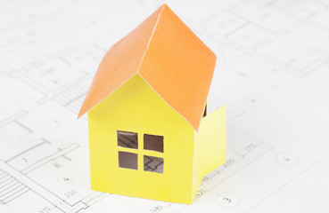 Paper model of the house costs on the construction plan