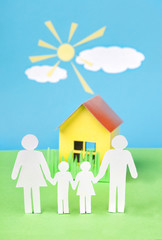 Paper cut of family with house  on green grass