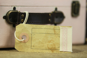 blank luggage tag on vintage suitcase