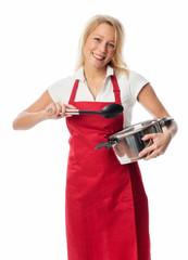 Hausfrau mit Schürze hält einen Topf und einen Löffel