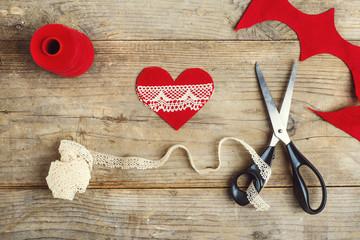 Handmade felt heart on a wooden floor.