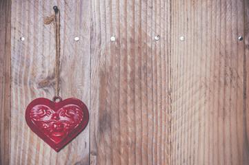 Coeur rouge en métal sur du bois