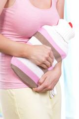 Frau mit Wärmflasche und Unterleibsschmerzen