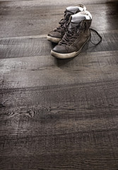 Dirty old shoes on wooden floor